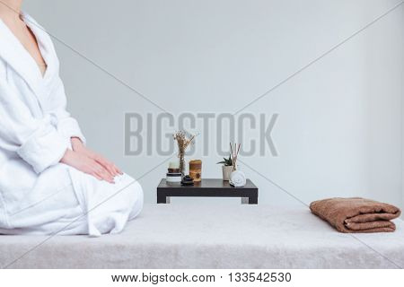 Closeup of young woman in bathrobe sitting on massage table in spa salon