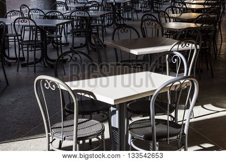 Terrace with tables and chairs in colonnade in Acqui Terme in Piedmont Italy