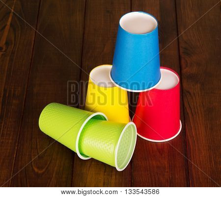 Multi-colored disposable paper and plastic cups on the background of dark wood.
