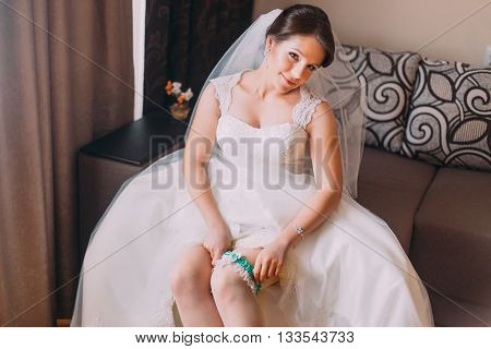 Close up portrait of beautiful caucasian mid adult bride dressing her garter.