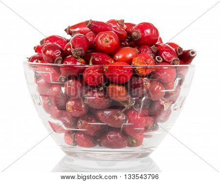 Are dry dog rose berries in a glass bowl isolated on white background.