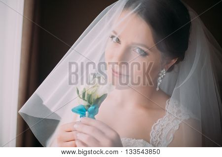 Indoor portrait of sensual, very beautiful bride in veil, holding cute little boutonniere, close-up.
