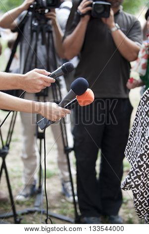 TV interview. Journalists holding microphones conducting TV or radio interview