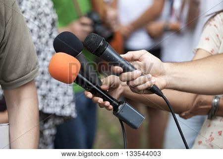 Journalists holding a microphones conducting TV or radio interview. News conference.
