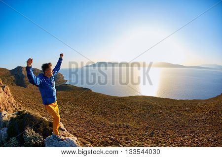 man standing on a cliff against a blue sea