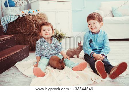 Young Children Playing With A Rabbit In The Room. The Concept Of Happiness, Joy And Family Values