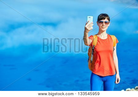 female traveler with backpack standing on the cliff against sea and blue sky at early morning. Balos beach on background, Crete, Greece. Woman taking a selfie photo in smartphone