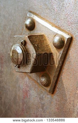 Big and ancient rusty metal nut locked