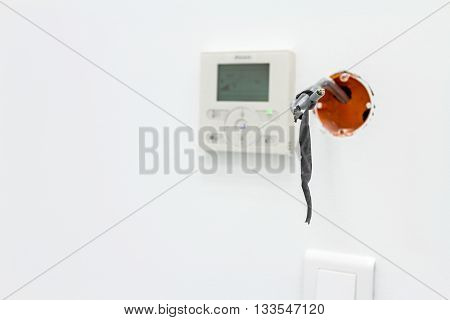 Modern digital electronic thermostat climate control system in background. Unfinished electrical or system outlet socket plug in. Exposed wiring in an unfinished plug socket