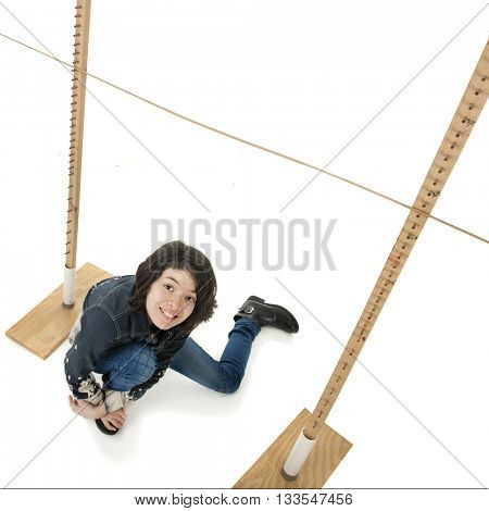 An overhead view of a young teen girl who has fallen under a limbo stick.  On a white background.