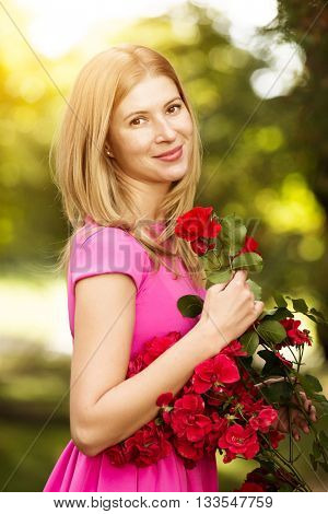 Young spring fashion woman with roses in spring garden. Springtime. Trendy girl at sunset in spring landscape background. Allergic to pollen of flowers. Spring allergy
