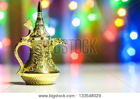 Golden Arabic Coffee pots in colorful illuminated background. Ramadan and Eid concept background