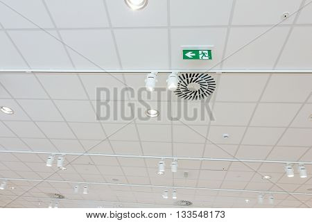 Standard international symbol safe exit sign is hanging from the ceiling of the modern office ceiling with air duct and lamps.