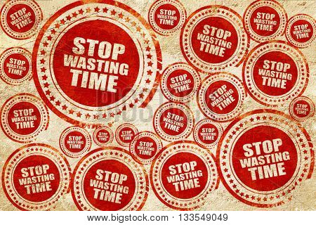 stop wasting time, red stamp on a grunge paper texture