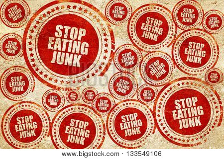 stop eating junk, red stamp on a grunge paper texture