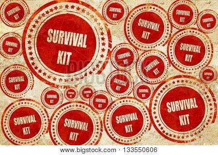 Survival kit sign, red stamp on a grunge paper texture