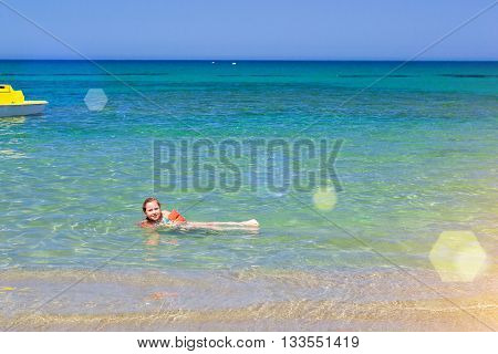 Cute happy girl child relaxing and bathed on the shores of Cretan sea in rescue arm cover. Sunny sandy Livadi beach in sea Bay of resort village Bali Rethymno Crete Greece