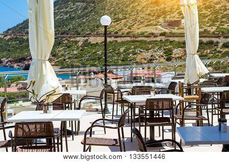 BALI GREECE - APRIL 28 2016: White tables with wicker chairs outside on veranda of restaurant overlooking the Cretan sea. Resort hotel Atali Village 4 star Bali Rethymno Crete Greece