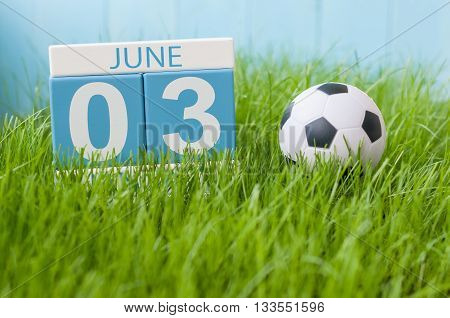 June 3rd. Image of june 3 wooden color calendar on green grass background with football outfit. Summer day.