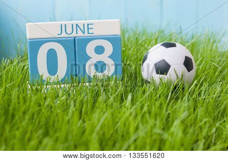 June 8th. Image of june 8 wooden color calendar on green grass background with football outfit. Summer day.