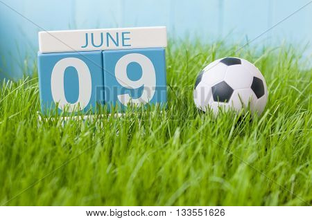 June 9th. Image of june 9 wooden color calendar on green grass background with football outfit. Summer day.