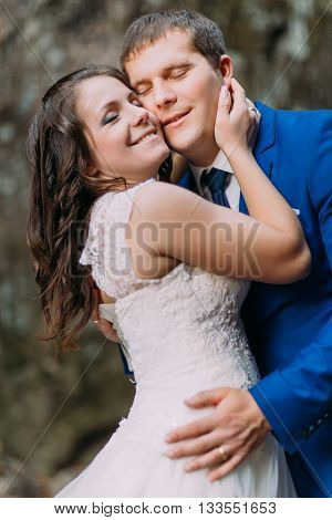 Closeup portrait of happy groom hugging with his bride. Rough blurry background.