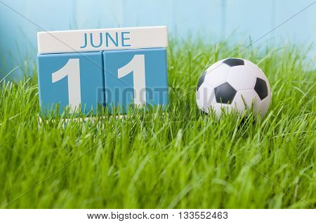 June 11th. Image of june 11 wooden color calendar on green grass background with football outfit. Summer day.