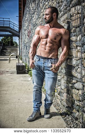 Handsome Muscular Shirtless Hunk Man Outdoor in City Setting. Showing Healthy Body While Looking Away to a Side, Leaning against Stone Wall