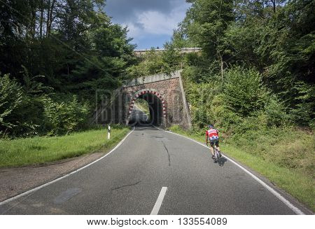 BOPPARD GERMANY 8 AUGUST 2014 - Cyclist on the road approaching a railway bridge in Germany