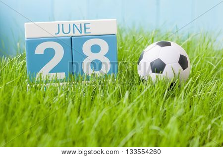 June 28th. Image of june 28 wooden color calendar on green grass background with football outfit. Summer day.