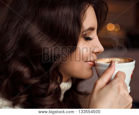Beauty portrait of a woman drinking coffee. The concept of delicious coffee, cappuccino, mochaccino, mocha. Amazing brunette girl with wavy hair holding a Cup of coffee at lips, enjoying the flavor
