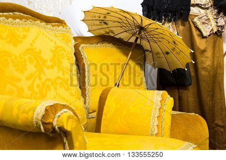 Unique background of old fashion arm chair with yellow upholstery and parasol placed beside it by vintage clothing hanging against wall