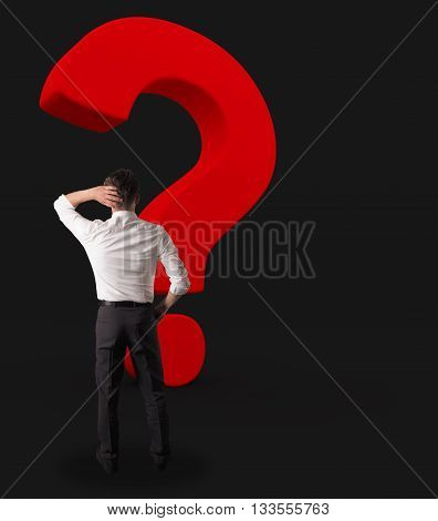 Business man with a big red Question mark on a dark background
