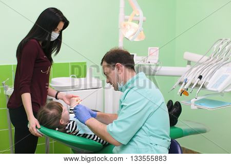happy male dentist with toothbrush and jaw layout showing how to brush teeth to patient girl and her mother at dental clinic office
