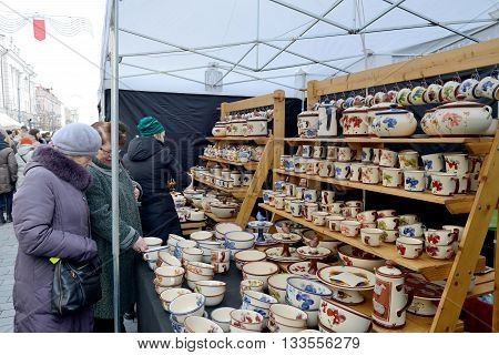 VILNIUS LITHUANIA - MARCH 6: Unidentified people trade typical lithuanian clay pots in annual traditional crafts fair - Kaziuko fair on Mar 6 2015 in Vilnius Lithuania