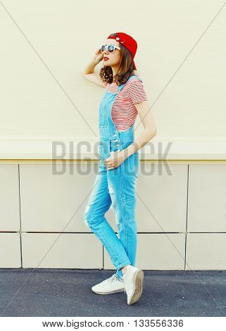 Fashion Pretty Woman Model In Denim Jumpsuit Standing Over White Background