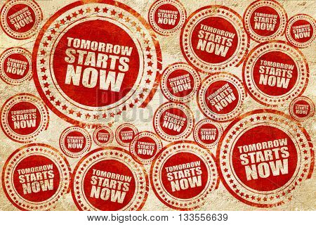 tomorrow starts now, red stamp on a grunge paper texture