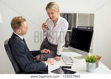 Secretary flirting with her boss in the office