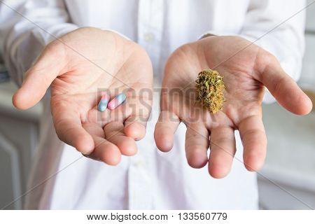 Doctor hand offering bud of medical cannabis and pills. Concept of choise of traditional medications and cannabis