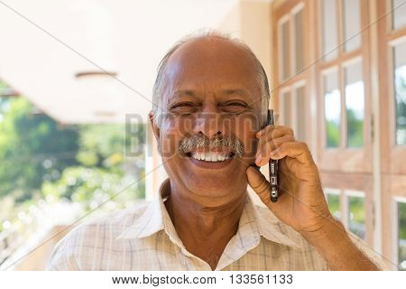 Closeup portrait happy bald pensioner enjoying phone conversation. Call me on my cell phone isolated outdoors outside background