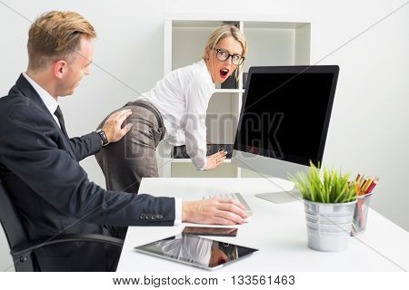 Business man touching secretaries butt in the office
