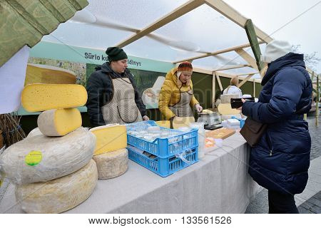 VILNIUS LITHUANIA - MARCH 7: Unidentified people trade home made cheese in annual traditional crafts fair - Kaziuko fair on Mar 7 2015 in Vilnius Lithuania