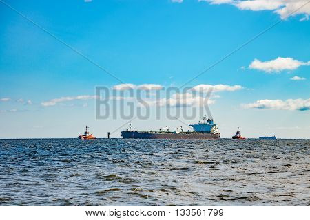 Tanker ship and tugboats moving in the sea.