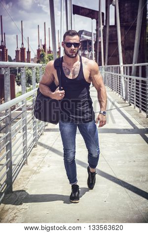 Handsome muscular man standing in city setting looking away to a side, carrying large sports bag on shoulder