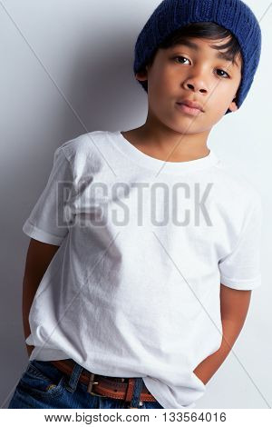 Portrait of a young mixed race boy wearing a white tee shirt and a knit hat.