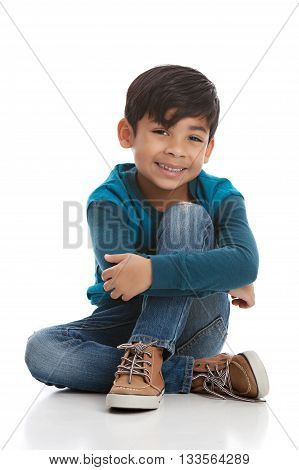 Full length portrait of a young mixed race boy sitting on the floor. Isolated on white.