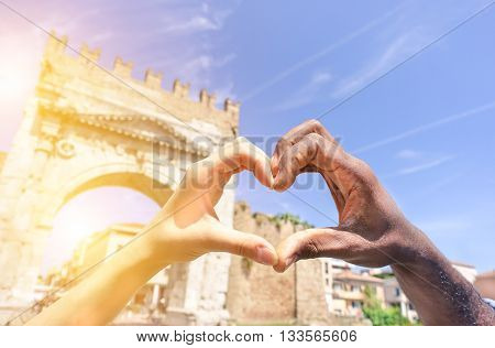 Closeup of woman and man hands showing heart shape during romantic vacation - Young multiracial couple making love symbol next a roman monument - Multi ethnic relationships concept - Focus on hands