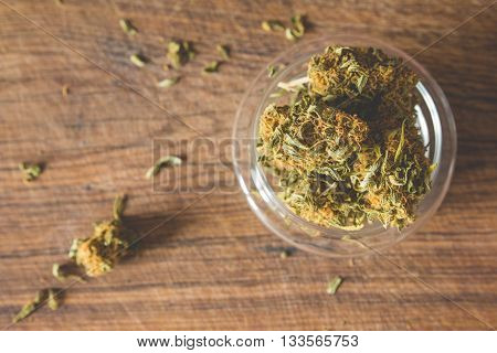 Marijuana buds in the glass plate on the wooden board