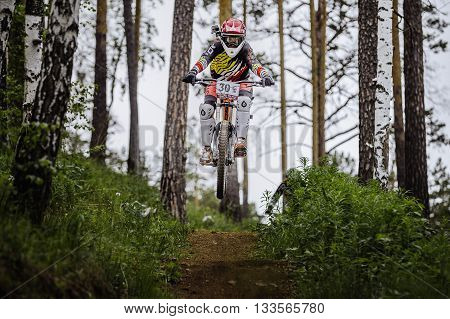 Miass Russia - May 29 2016: athlete racer bike jump with a mountain in forest on helmet video camera during Cup