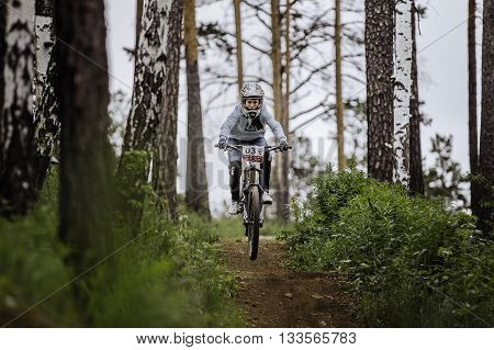 Miass Russia - May 29 2016: girl on mountain bike on bike rides on track in forest during Cup